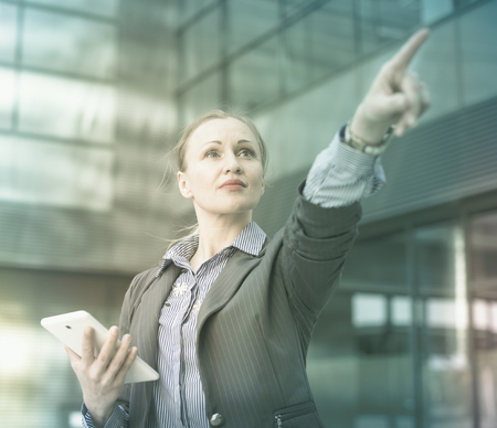 Professional woman in jacket with tablet pointing finger on object