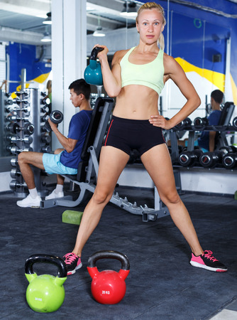 Portrait of sporty active woman exercising with dumbbells in gym