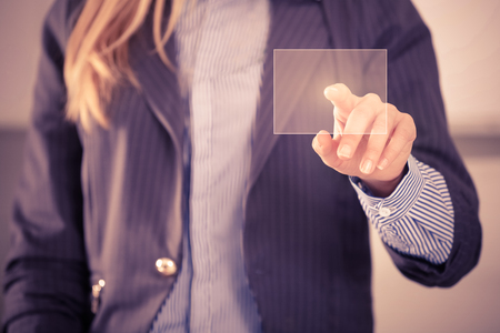 Woman touching screen on the background of modern glass buildings