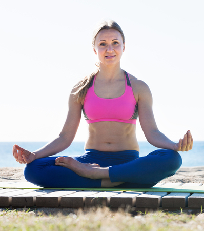 Positive sportswoman exercising asanas of yoga on the beach Stock Photo