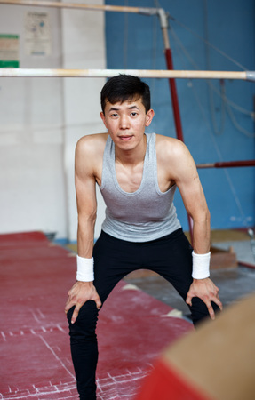 Young Asian athletic man posing near sports equipment in gym