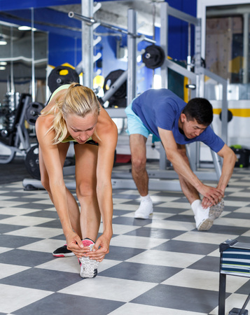 Positive fitness couple warming up during indoors stretching workout Stock fotó