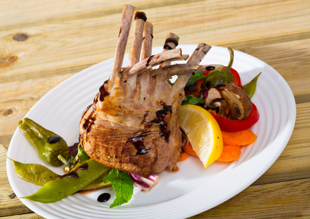 Delicious baked rack of lamb served on white plate with vegetables, mushrooms and greens seasoned with balsamic