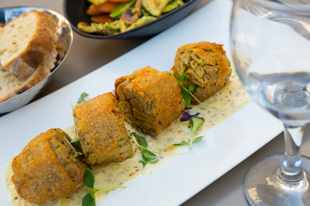 Piquant breaded Andouillette - traditional French sausage made with pork intestines or chitterlings and seasonings
