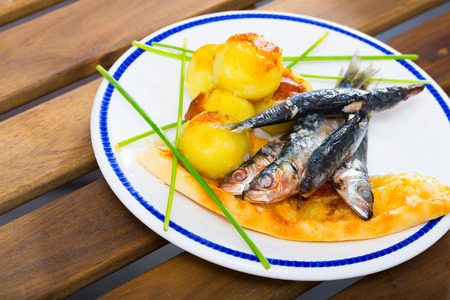 Image of  deliciously fried sprats with scone and potato croquettes on plate
