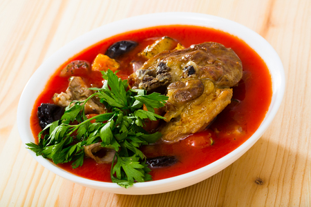 Savory tomato soup with mutton meat, vegetables, dried plums and apricots served with greens