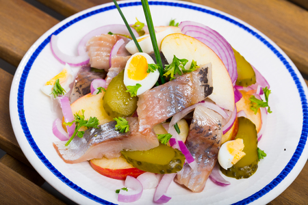 Marinated herring with sliced apples, cucumbers, onion - traditional dish of Norwegian cuisine