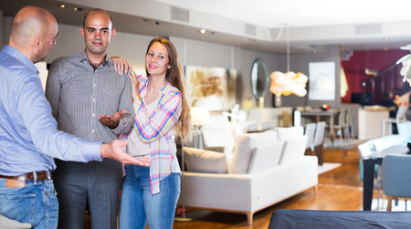 Family couple choosing furniture for apartment in salon with help of salesman