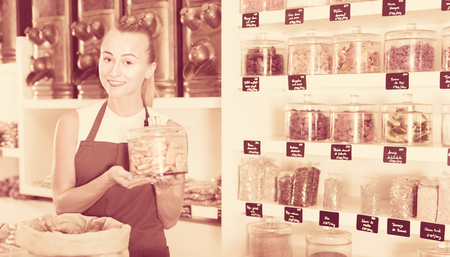 Young woman is offering dried fruits in container in the store. Archivio Fotografico