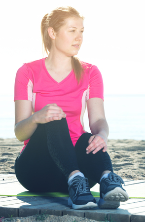 Sporty woman resting after training on ocean beach in sunny morning
