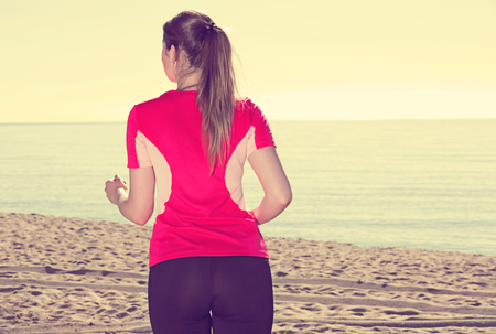 Positive svelte woman jogging during outdoor workout on beach