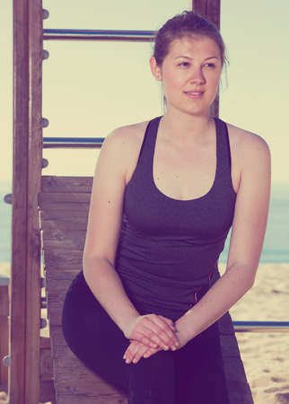 Young positive woman posing during morning training on beach