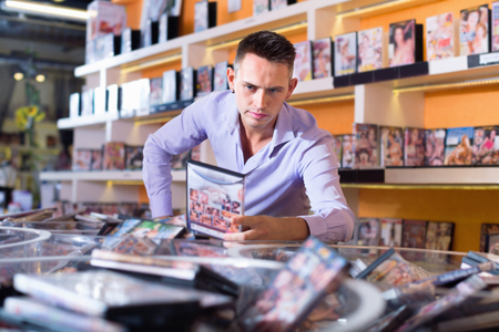 Glad positive male client selecting erotic video in shop and smiling Stock Photo
