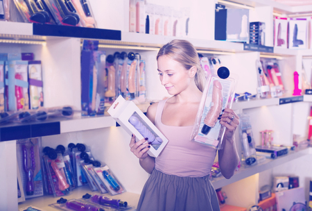 Portrait of happy young woman choosing big erotic toys in sex shop Reklamní fotografie