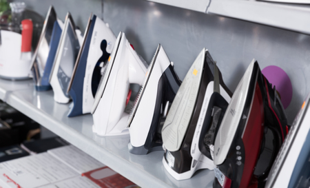 Picture of assortment of different modern irons at household appliances store