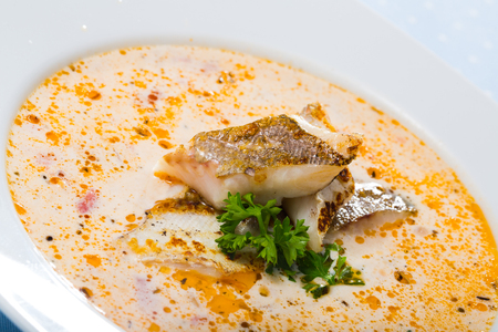 Image of tasty creamy soup with white fish cod and greens at white plate
