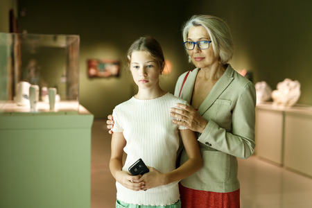 Intelligent female tutor helping tweenage girl exploring art pieces in art museum