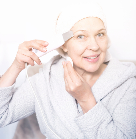 Mature woman getting face cleaned with ultrasonic device at home Stock fotó