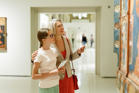 Attentive tween girl with senior woman looking with interest at gallery exposition Banque d'images