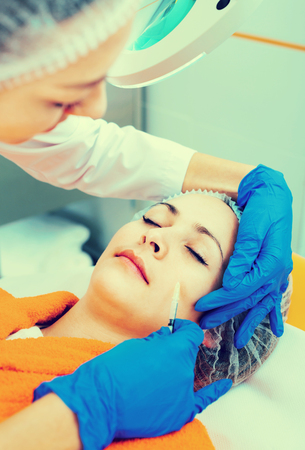 Positive female doctor doing beauty injection to young woman client
