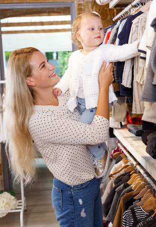 Young attractive woman and her little daughter buying kids clothes in shop