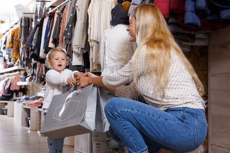 Portrait of mother and her little daughter with paper shopping bags in kids clothing shop