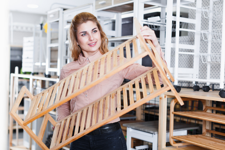 Modern female housewife buying 2-tier wood household shelves in store Stock Photo