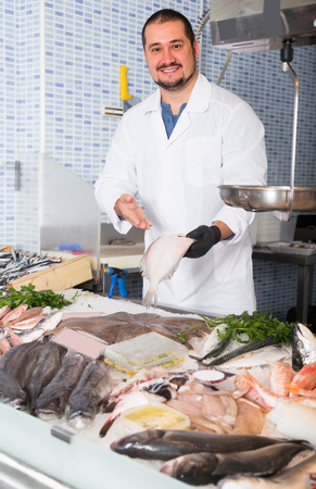 Seller in white cover-slut holding fish in his hand in supermarket