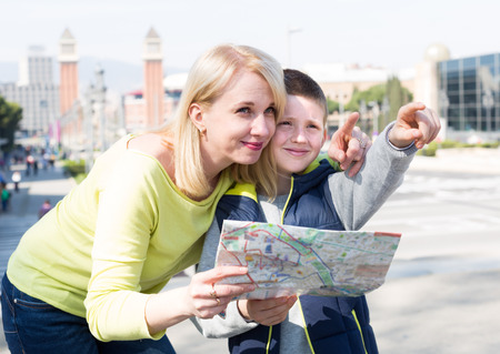 Smiling mother and son looking at map guide during sightseeing tour Banco de Imagens