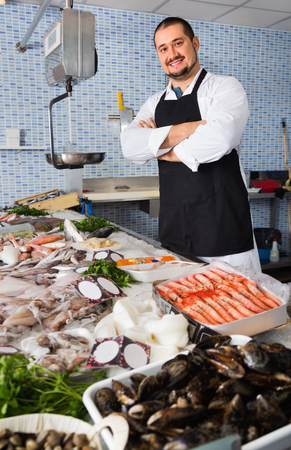 Cheerful positive seller in black apron showing fish on his counter in supermarket