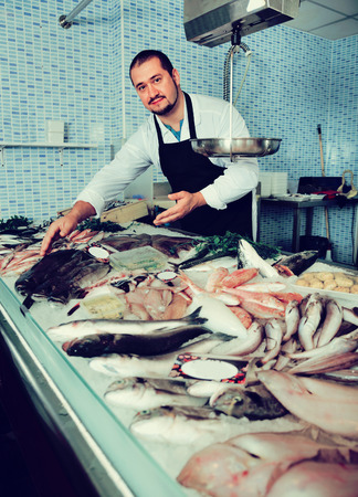 Friendly seller in black apron shows fish counter