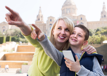 Young mother and son paying attention to sight during sightseeing tour