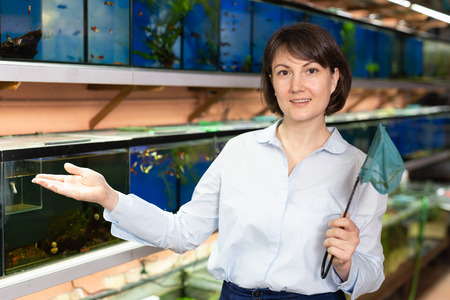Portrait of friendly pet shop saleswoman standing on background of aquariums with fish Stock fotó