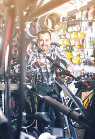 Biker is looking for bicycle handlebars in sports shop.
