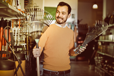 Smiling positive man choosing various tools in garden equipment shop