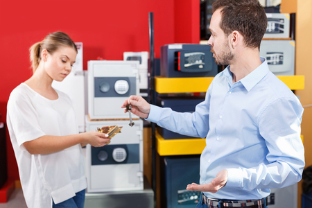 Upset  serious couple choosing door lock for their apartment in store