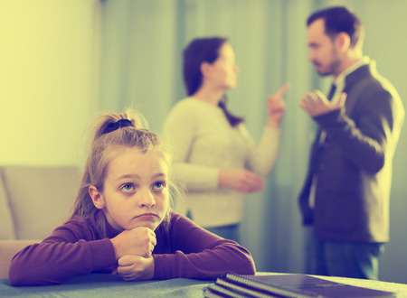 Adult male and female arguing with each other while their daughter at home