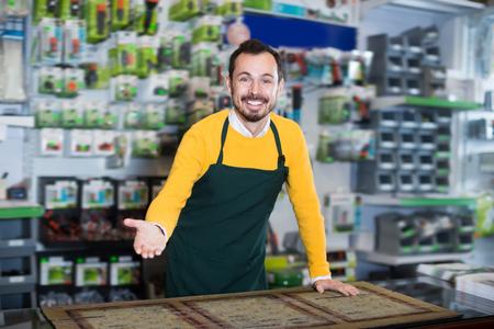 Positive male seller demonstrating assortment in garden equipment shop