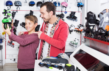Smiling father and son examining various a roller-skates at a sports store. Focus on man Фото со стока - 118999947
