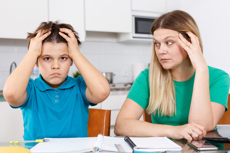 Annoyed mother helping son with homework sitting nearby at kitchen table Stock Photo