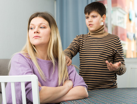 Upset mother sitting at table after arguing with son in domestic interior
