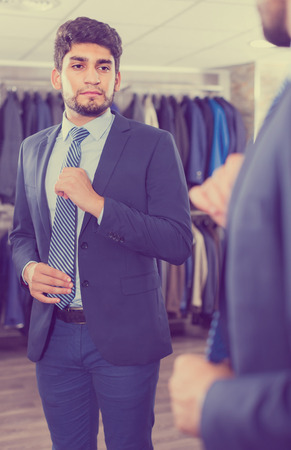Adult male is trying on tie in front of the mirror in mens shop. Zdjęcie Seryjne