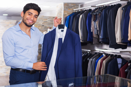 Man is demonstrating his choice of suit in apparel shop