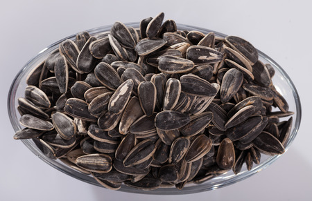Top view of glass bowl with sunflower seeds in hulls on white background