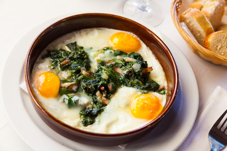 Delicious fried eggs with spinach, ham and raisins in clayware. Traditional Catalan dish