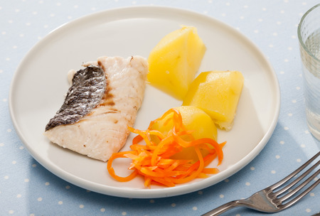 Steamed whiting fish with vegetable garnish of cooked potato and grated boiled carrots. Diet and health concept