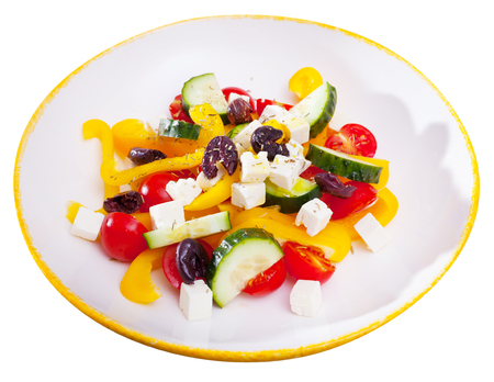 Fresh colorful Greek salad (horiatiki salad) served with feta cheese on white plate. Isolated over white background