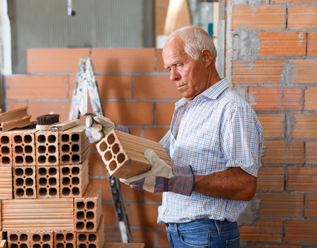 Focused elderly man working on his home renovations, checking brick for masonry