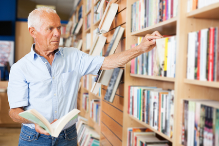 positive mature man absorbedly searching for interesting books on racks in bookstore