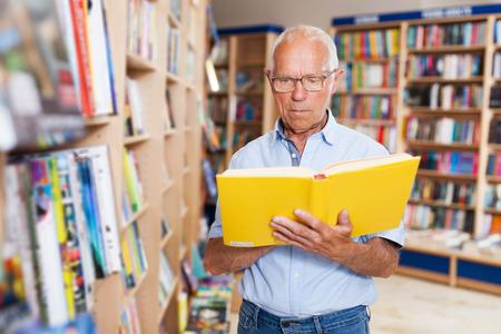 glad serious mature man reading new books in bookshop Foto de archivo